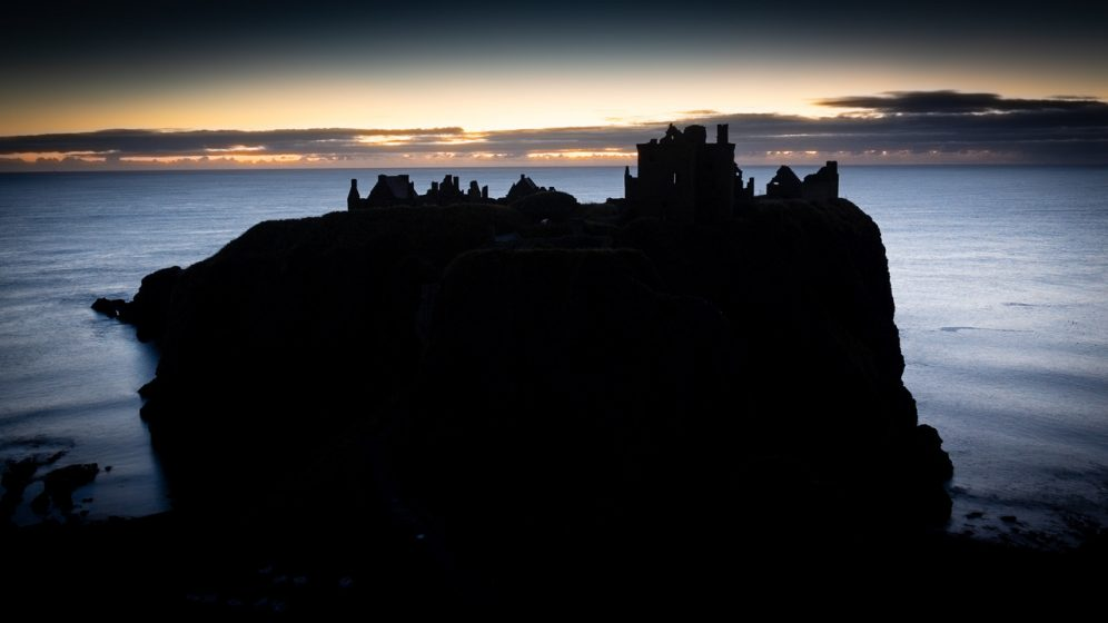 Castle suspended in the ocean, with dawn behind.