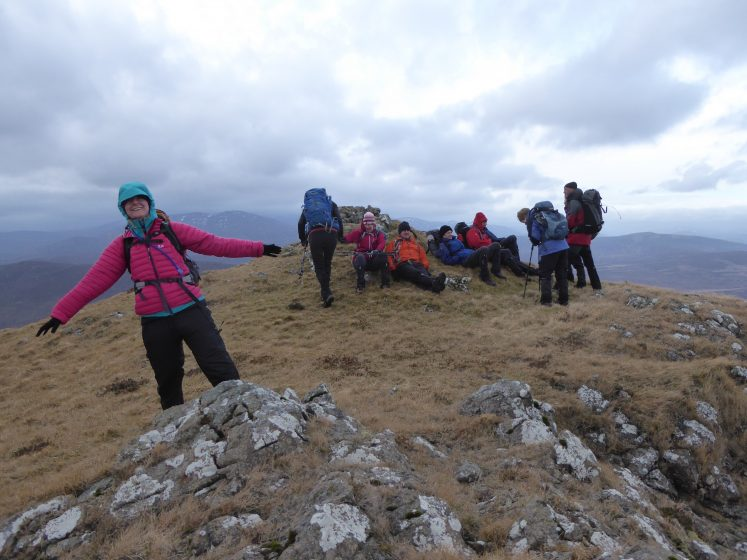 Group of walkers on windy hill summit with craggy rock outcrops