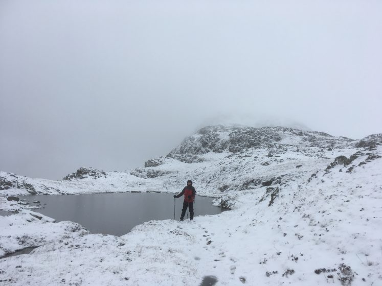 lone climber standing beside corrie at snow top mountain peak
