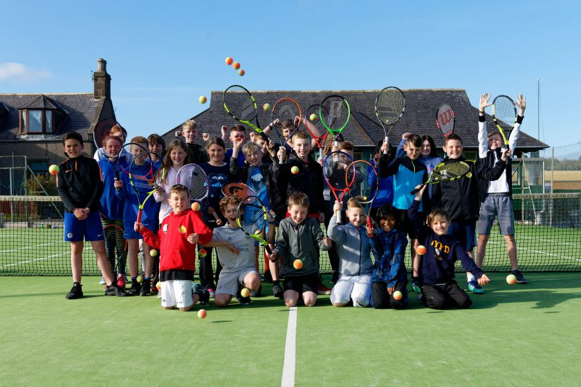 a lively group of youngsters waving tennis racquets