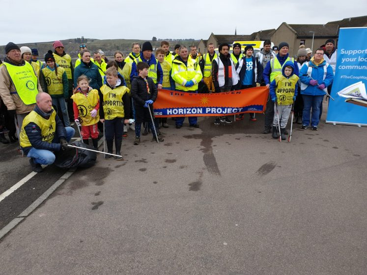 large group of people with yellow hi-vis vests on and litter picking equipment