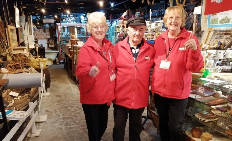 Three pleased volunteers in their red fleeces