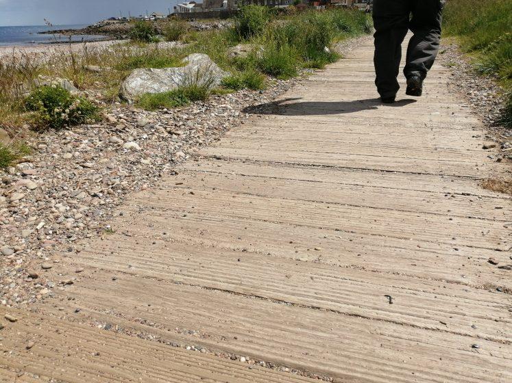 low level shot of man walking on boardwalk