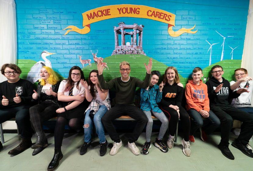 Comedian and carer pupils in front of mural which shows Stonehaven images