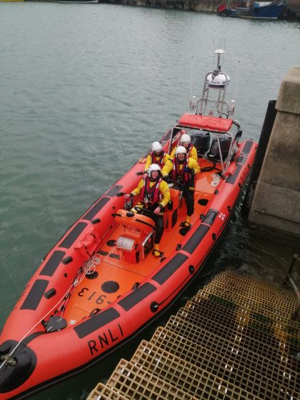 The new orange rigid inflatable boat at the harbour side