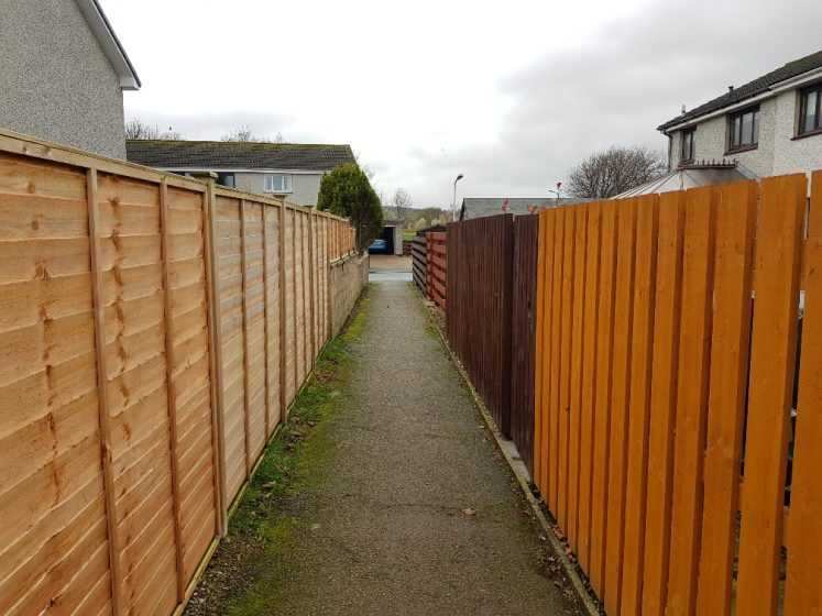 long straight path lined by high wooden fences