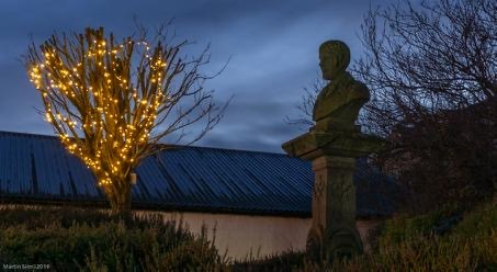 Dusky sky, tree draped with lights and silhouette of Burns' statue