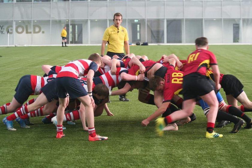 A rugby scrum with ref looking on