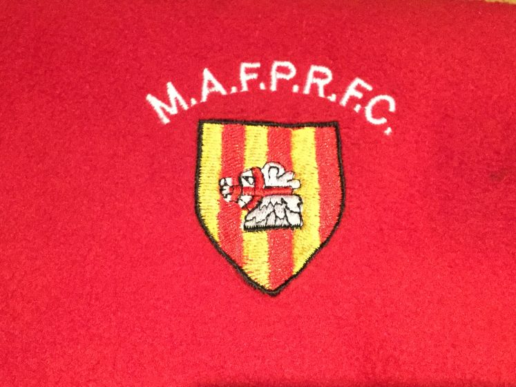 photo of embroidered Mackie badge on red background