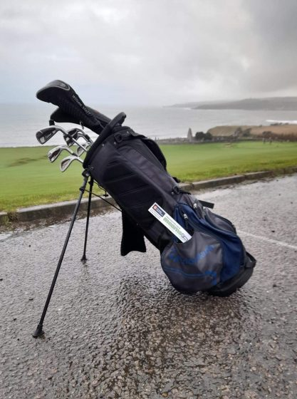 golf clubs in bag with course behind