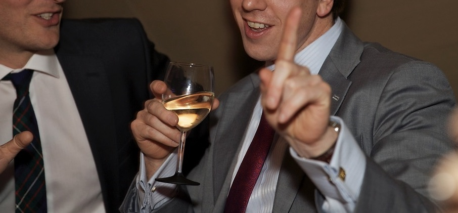man holding glass of wine and raising finger as if to say tut tut
