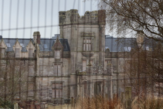grim image of partly restored house through security fencing